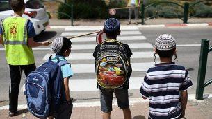 تلاميذ يقفون أمام ممرة مشاة قبل مغادرة المدرسة في بيت إيل، 1 مايو، 2019. (Gili Yaari /Flash90)