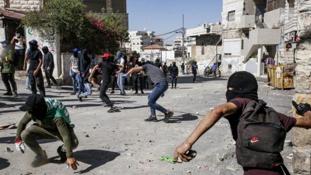 فلسطينيون يرشقون الحجارة خلال اشتباكات مع الشرطة في حي العيساوية في القدس الشرقية، 28 يونيو 2019 (Hazem Bader/AFP)