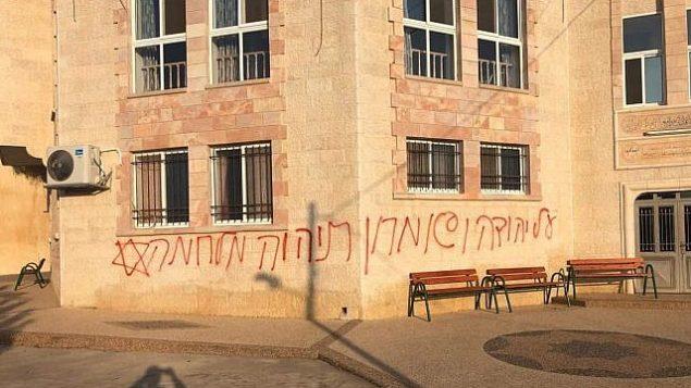 عبارة 'ستكون هناك حرب على يهودا والسامرة' على جدار مبنى في قرية كفر مالك الفلسطينية في الضفة الغربية، 17 يونيو 2019 (Kafr Malik Municipality)