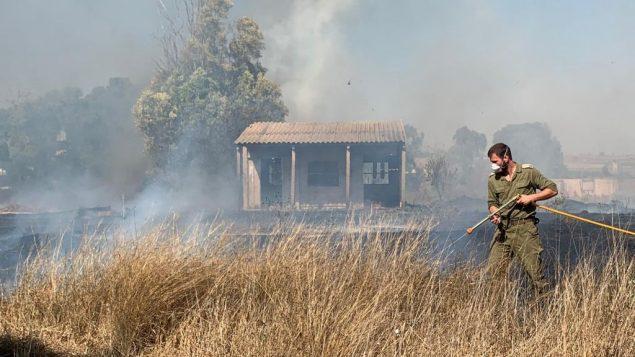 جندي إسرائيلي يعمل على إخماد حريق ناجم عن بالونات حارقة تم إطلاقها من قطاع غزة في أحد الحقول في منطقة شاعر هنيغف جنوب إسرائيل، 27 يونيو، 2019.  (Sha'ar Hanegev regional council)