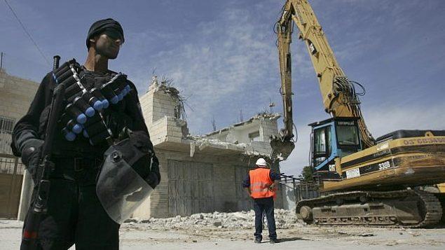 توضيحية: شرطي إسرائيل يقف بالقرب من جرافة خلال هدم منزل فلسطيني في حي صور باهر بالقدس الشرقية، 7 أبريل، 2009.  (Kobi Gideon / FLASH90)