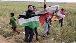 اطفال فلسطينيون يلوحون بالعلم الفلسطيني بينما يحرقون صورة الرئيس الامريكي دونالد ترامب، خلال مظاهرة ضخمة بالقرب من مدينة خان يونس في جنوب قطاع غزة، 30 مارس 2018 (Said Khatib/AFP)