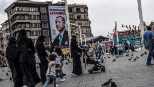 توضيحية: مارة يمرون من أمام صورة للرئيس التركي رجب طيب إردوغان كُتب عليها 'شكرا لك إسطنبول'، في ساحة تقسيم في إسطنبول، 28 يونيو، 2018.  (AFP Photo/Bulent Kilic)