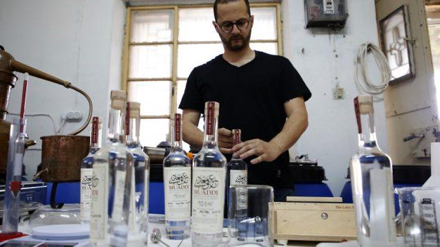 نادر معدي يقوم بتعبئة زجاجات العرق التي ينتجها في بلدة بيت جالا في الضفة الغربية، بالقرب من بيت لحم، 16 يونيو، 2019.  (HAZEM BADER / AFP)