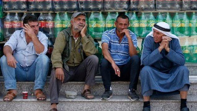 رجال فلسطينيون يتحادثون خلال تظاهرة ضد القمة الاقتصادية المنعقدة في البحرين برعاية أمريكية في مدينة يطا بالقرب من مدينة الخليل بالضفة الغربية، 24 يونيو، 2019. (HAZEM BADER / AFP)