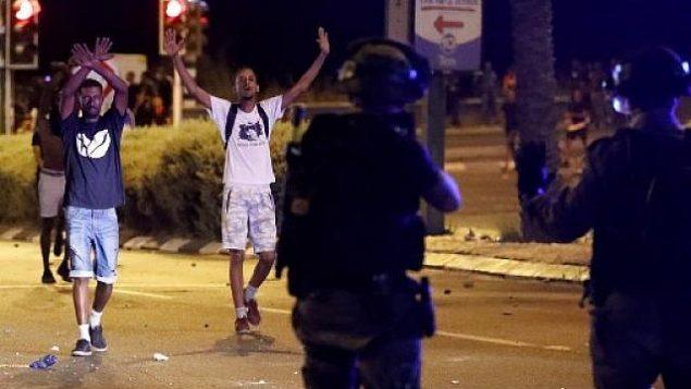 أفراد من المجتمع الإثيوبي في إسرائيليين في مواجهة رجال شرطة خلال اشتباكات في مدينة نتانيا الساحلية في 2 يوليو، 2019، خلال احتجاجات على مقتل الشاب سولومون تيكاه برصاص شرطي خارج الخدمة.( JACK GUEZ / AFP)