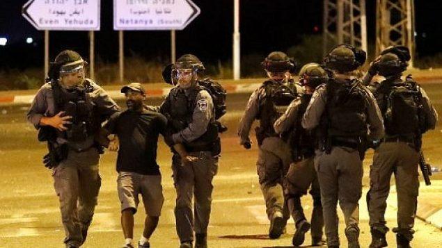 الشرطة تعتقل أحد أفراد المجتمع الإثيوبي في إسرائيل خلال اشتباكات في مدينة نتانيا الساحلية في 2 يوليو، 2019، خلال احتجاجات على مقتل الشاب سولومون تيكاه برصاص شرطي خارج الخدمة.( JACK GUEZ / AFP)