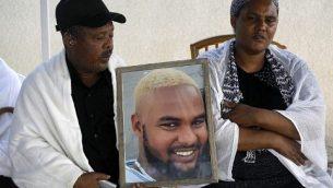 ووركا ووبيج تيكاه يحملان صورة ابنهما سولومون تيكاه (19 عاما)، الذي قُتل برصاص شرطي خارج الخدمة في 1 يوليو 2019، داخل منزلهما في مدينة حيفا، 3 يوليو 2019 (MENAHEM KAHANA / AFP)