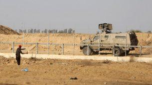 متظاهر فلسطيني يلقي زجاجة حارقة باتجاه مركبة عسكرية اسرائيلية خلال مظاهرات عند حدود غزة، 5 يوليو 2019 (SAID KHATIB / AFP)