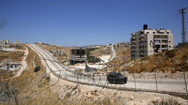 صورة التقطت من قرية بيت ساحور الفلسطينية في الضفة الغربية، تظهر سيارة شرطة اسرائيلية تمر بجانب منازل تم اصدار اوامر بهدمها، في حي صور باهر في القدس الشرقية، 11 يوليو 2019 (HAZEM BADER/AFP)