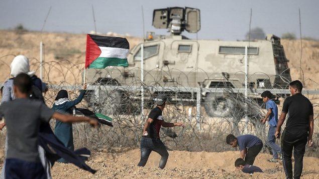 متظاهرون فلسطينيون يلقون الحجارة باتجاه القوات الإسرائيلية خلال مظاهرات عند الحدود مع اسرائيل، شرقي خان يونس، جنوب قطاع غزة، 12 يوليو 2019 (Mahmud Hams/AFP)
