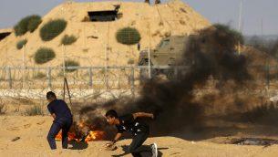 صورة توضيحية: منظاهرون فلسطينيون يحرقون إطارات خلال اشتباكات بين المتظاهرين الفلسطينيين والقوات الإسرائيلية عبر السياج الشائك خلال مظاهرة حدودية بالقرب من رفح جنوب قطاع غزة في 19 يوليو،  2019.  (SAID KHATIB / AFP)
