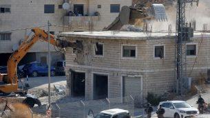 صورة التقطت من الضفة الغربية في 22 يوليو، تظهر قوات الامن الإسرائيلية تهدم احد المباني الفلسطينية التي كانت قيد البناء والتي صدرت اوامر بهدمها في منطقة وادي الحمص المتاخمة لقرية صور باهر الفلسطينية في القدس الشرقية (Hazem BADER / AFP)