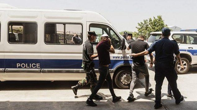 سياح إسرائيليون، مشتبهون باغتصاب فتاة بريطانية (19 عاما) في أيا نابا، يغادرون قاعة المحكمة فيمدينة بارليمني السياحية شرق جزيرة قبرص، 26 يوليو، 2019. (Iakovos Hatzistavrou / AFP)