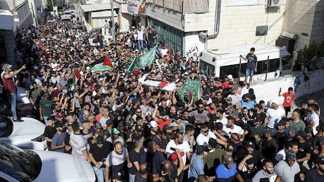 مشيعون يرفعون الأعلام الفلسطينية وأعلام حماس خلال جنازة الشاب الفلسطيني محمد عبيد (20 عاما)، الذي قُتل في 27 يناير في مواجهات مع الشرطة الإسرائيلية، القدس الشرقية، 1 يوليو، 2019.   (AP Photo/Mahmoud Ilean)