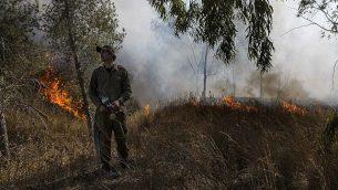 جندي إسرائيلي يحاول إخماد نيران ناجمة عن بالونات حارقة تم إطلاقها من قطاع غزة في جنوب غزة، 26 يونيو، 2019.  (AP Photo/Tsafrir Abayov)