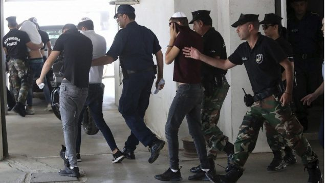 مشتبه بهم اسرائيليون يغطون وجوههم بمساعدة ملابسهم اثناء وصولهم الى محكمة فاماغوستا في بلدة بارالامني في قبرص، 26 يوليو 2019 (AP Photo/Petros Karadjias)