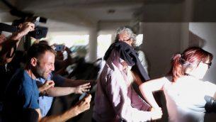 شرطية ترافق شابة بريطانية (19 عاما) الى محكمة مقاطعة فاماغوستا في بارالميني في شرق قبرص، 29 يوليو 2019 (AP Photo/Petros Karadjias)