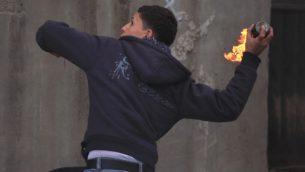 صورة توضيحية: فلسطيني يلقي زجاجة حارقة (Issam Rimawi/Flash90)