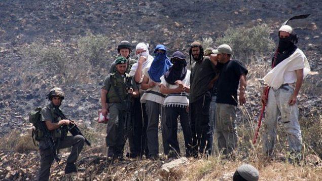 مستوطنون ملثمون إسرائيليون من يتسهار وجنود يراقبون حقولا فلسطينية تم إشعال النار في قرية عصيرة القبلية، 2 يونيو، 2010.  (Wagdi Ashtiyeh/Flash90)