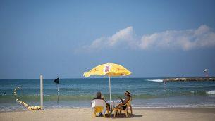 توضيحية: شخصان يستجمان على الشاطئ في تل أبيب في يوم صيفي حار، 29 أغسطس، 2018. (Miriam Alster/FLASH90)