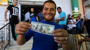 فلسطينيون يتلقون مساعدات مالية كجزء من مبلغ 480 مليون دولار خصصته قطر لمساعدة الفلسطينيين، في مكتب بريد في مدينة غزة، 19 مايو، 2019. (Abed Rahim Khatib/Flash90)