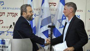 مصافحة بين رئيس الوزراء الأسبق إيهود براك (يسار) ويائير غولان بعد الإعلان عن تشكيل حزب جديد في 'بيت سوكولوف' في تل أبيب، 26 يونيو، 2019. (Jacob Magid/Times of Israel)