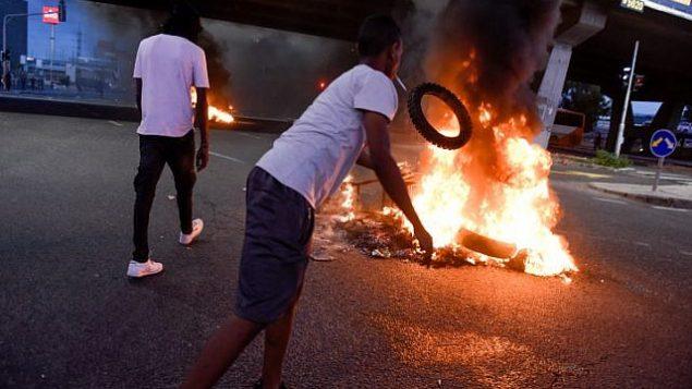 إسرائيليون من أصول إثيوبية ونشطاء يتظاهرون في أعقاب مقتل الشاب من أصول إثيوبية، سولومون تيكاه (19 عاما)، برصاص شرطي خارج الخدمة في كريات يام في الليلة السابقة، بالقرب من كريات آتا، 1 يوليو، 2019.  (Meir Vaknin/Flash90)