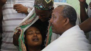 ووركا تيكاه (يمين)، والد سولومون تيكاه (19 عاما)، الذي قُتل برصاص شرطي، خلال جنازة ابنه في كريات حاييم، وتقف بجانبه امرأة تحاول تهدئة ابنته (يسار)، 2 يوليو، 2019. (Yonatan Sindel/Flash90)