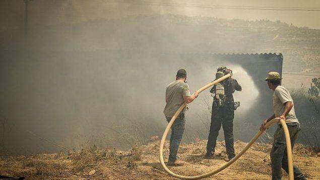 متطوعون يحاولون اخماد حريق في مستوطنة شافي شومرون في الضفة الغربية، 17 يوليو 2019 (Sraya Diamant/Flash90)