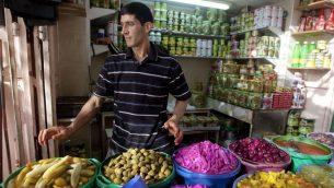 الطعام، بما في ذلك الخضراوات والزيتون المخللة، في أحد أسواق مدينة الخليل في الضفة الغربية، 28 يونيو، 2014.  (photo credit: AP/Majdi Mohammed)