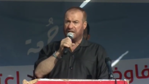 القيادي في 'حماس'، فتحي حماد، يتحدث لفلسطينيين في المنطقة الحدودية بين إسرائيل وقطاع غزة في 12 يوليو، 2019.  (Adam Rasgon/Times of Israel)