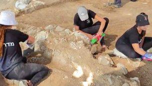 شباب محليون يشاركون في حفريات أثرية كشفت عن مسجد يعود إلى أوائل القرن السابع-الثامن بالقرب من رهط قبل عمليات توسيع لحي في المدينة، يوليو 2019. (Anat Rasiuk/Israel Antiquities Authority)