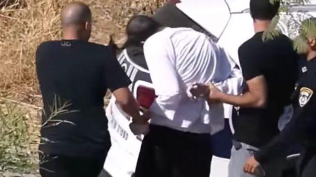 شرطي يشد رجل يهودي متشدد من شعره خلال مظاهرة في بيت شيمش، 6 يوليو 2019 (Facebook screenshot)