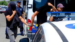 اثنين من المشتبه بهم باغتصاب جماعي لسائحة بريطانية يغطون وجوههم بمساعدة ملابسهم اثناء وصولهم الى محكمة فاماغوستا في بلدة بارالامني في قبرص، 18 يوليو 2019 (AP Photo/Petros Karadjias)