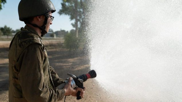 جندي اسرائيلي يستخدم خرطوم اطفاء (Israel Defense Forces)