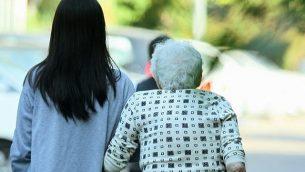 صورة توضيحية لعاملة فلبينية تقدم المساعدة لسيدة مسنة في 2 نوفمبر، 2010. (Moshe Shai/Flash90)