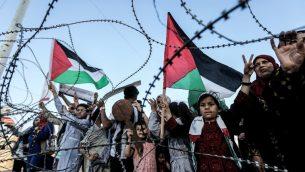 طفلة ترفع علم فلسطيني، بينما يرفع طفل اخر مفتاح خشبي يمثل حق العودة، خلف اسلاك شائكة عند الحدود بين قطاع غزة واسرائيل، شرقي مدينة غزة، 13 مايو 2018 (AFP/Mahmud Hams)