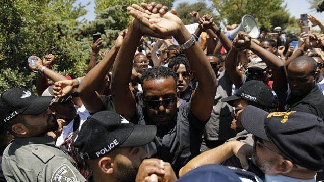 إسرائيليون من أصول إثيوبية يتظاهرون أمام الكنيست في القدس في 15 يوليو، 2019، بعد إطلاق سراح شرطي قتل شابا من أصول إثيوبية بعد إطلاق النار عليه في مدينة حيفا في 30 يونيو، 2019.  (Menahem Kahana/AFP)