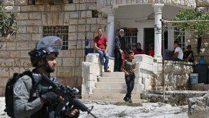 فلسطينيون يراقبون جنودا إسرائيليين خلال عملية بحث من بيت إلى بيت في قرية بيت فجار بالقرب من بيت لحم بالضفة الغربية، 8  أغسطس، 2019، في أعقاب هجوم طعن.  (HAZEM BADER / AFP)