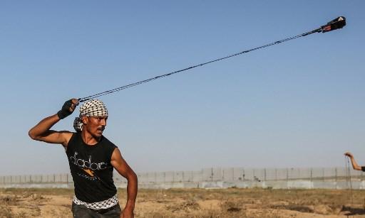 متظاهر فلسطيني يستخدم مقلاعا لرشق الحجارة باتجاه القوات الإسرائيلية بالقرب من السياج الحدودي بين اسرائيل وقطاع غزة، 16 اغسطس 2019 (MAHMUD HAMS / AFP)