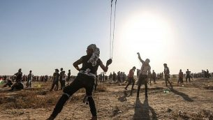 متظاهر فلسطيني يستخدم مقلاع لرشق الحجارة باتجاه القوات الإسرائيلية بالقرب من السياج الحدودي بين اسرائيل وقطاع غزة، 16 اغسطس 2019 (MAHMUD HAMS / AFP)