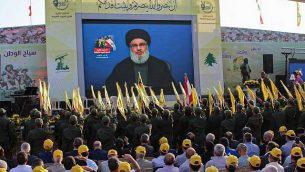 مناصرو منظمة حزب الله الشيعية اللبنانية يحتشدون لمتابعة نقل كلمة الأمين العام للمنظمة، حسن نصر الله، على شاشة كبيرة في بلدة العين في منطقة سهل البقاء اللبنانية، 25 أغسطس، 2019. (AFP)