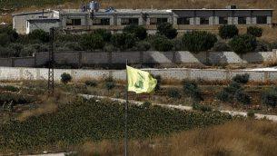 صورة تم التقاطها في 26 أغسطس، 2019، بالقرب من موشاف أفيفيم على الحدود الشمالية لإسرائيل يظهر فيها علم حزب الله في قرية عيترون اللبنانية.  (Jalaa Marey/AFP)