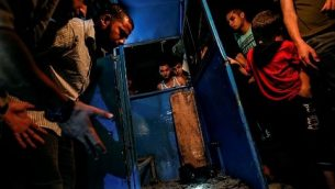 فلسطينيون يتفرجون على كشك مدمر لحاجز شرطة وقع فيه انفجار في مدينة غزة، 27 أغسطس، 2019.  (Photo by MAHMUD HAMS / AFP)