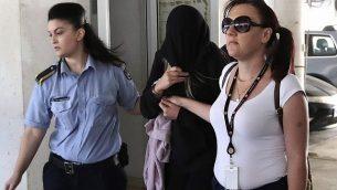 شرطيتان ترافقان شابة بريطانية (19 عاما)، وسط، خارج محكمة فاماغوستا في مدينة بالارميني القبرصية، 29 يوليو، 2019.  (AP/Petros Karadjias)