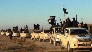 مقاتلي تنظيم الدولة الإسلامية يرفعون اسلحتهم ويلوحون بأعلام التنظيم في طريق مؤدية للعراق، في الرقة، سوريا، 2014 (Militant photo via AP, File)