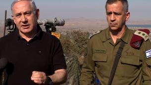 رئيس الوزراء بنيامين نتنياهو (يسار) يتحدث مع الصحافيين خلال جولة قام بها في هضبة الجولان برفقة رئيس هيئة أركان الجيش الإسرائيلي أفيف كوخافي في 25 أغسطس، 2019. (YouTube/Screen capture)