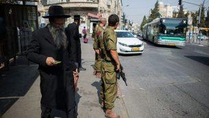 جنود إسرائيليون يقومون بحراسة محطة حافلات في حي 'مئة شعاريم' لليهود الحريديم في القدس، 19 أكتوبر، 2015. (Yonatan Sindel/Flash90)