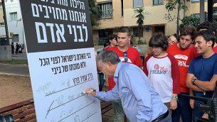 زعيم حزب 'العمل' عمير بيرتس يوقع على التزام للحزب بالقيم الإنسانية، تل أبيب، 4 أغسطس، 2019.  (Courtesy)